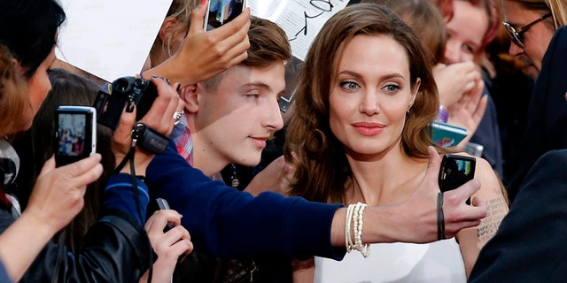 Angelina Jolie (C) poses for a selfie with a fan during the premiere of the film World War Z in Berlin June 4, 2013.