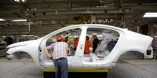 Workers prepare to assemble parts of a Volvo car at an assembly line of the new Volvo automobile manufacturing plant in Chengdu, Sichuan province, June 5, 2013. Chinese-owned Swedish automaker Volvo Car Corp expects to be selling 200,000 cars a year in China by 2018, a senior executive said, two years ahead of its latest target and as a new assembly plant gears up for full production later this year. REUTERS/Jason Lee (CHINA - Tags: TRANSPORT BUSINESS EMPLOYMENT) - RTX10CA4