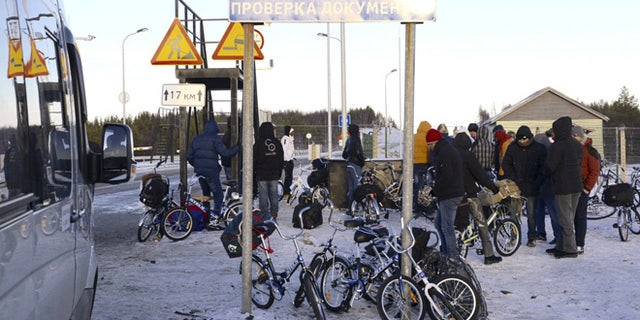 Oct. 30, 2015: Refugees and migrants gather near a check point on the Russian-Norwegian border.