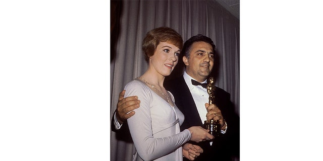 "Fellini is shown in this 1964 picture as he is presented by actress Julie Andrews the 1964 Oscar for ""Best Foreign Film"" for his film ""8-1/2."""