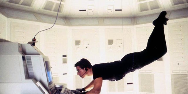 """Actor Tom Cruise is shown as he portrays """"Agent Ethan Hunt"""" in the adventure thriller film, """"Mission Impossible."""""""