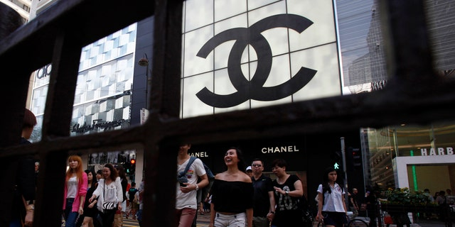 Shoppers walk across Canton Road, famous for its luxury brand stores, at Hong Kong's Tsim Sha Tsui shopping district May 9, 2013. Armed with empty suitcases and same-day return tickets, an army of mainland Chinese is descending on suburban outlet shopping malls and international fashion chains in Hong Kong, turning cheap into the new chic as luxury falls out of favour.  Picture taken May 9, 2013. To match HONGKONG-RETAILERS/  REUTERS/Bobby Yip (CHINA - Tags: BUSINESS) - RTXZTB2