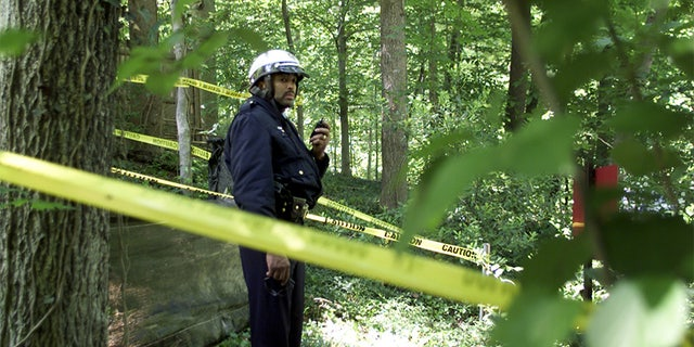 A Washington Metropolitan Police Officer stands behind police lines inRock Creek Park in Washington, May 22, 2002. A skull and other humanbones were found in the park early Wednesday and police are trying todetermine whether they are the remains of Chandra Levy, the 24-year-oldformer intern who disappeared more than a year ago. REUTERS/WilliamPhilpottWP/HB - RTR5HH0