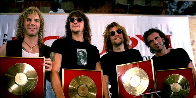 Members of the rock group Bon Jovi (L to R) David Bryan, Richie Sambora, Jon Bon Jovi and Tico Torres pose with golden discs presented to them by Polygram, one of India's largest music companies after their album registered record sales in Bombay.
