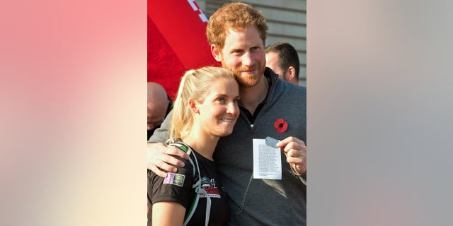 Britain's Prince Harry embraces Kirsty Ennis as he greets members of the Walking With The Wounded team as they arrive at Buckingham Palace in London, Britain November 1, 2015.