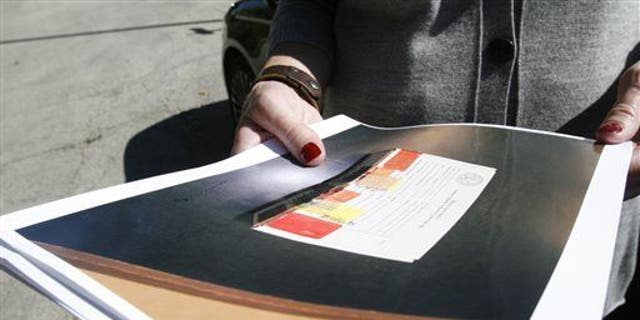 Cara Smith, the chief of policy and communications for the Cook County, Ill., Sheriff's department, holds a photo of a rape kit on Sept. 26, 2013, in Robbins, Ill.