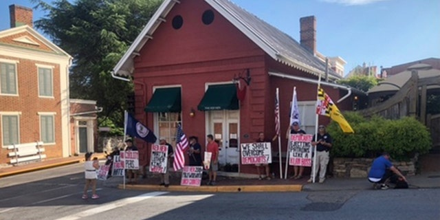 People gathered in front of The Red Hen to protest on the day of its reopening.