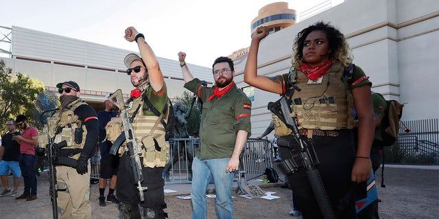 Members of the John Brown Gun Club and Redneck Revolt protest outside the Phoenix Convention Center, Tuesday, Aug. 22, 2017, in Phoenix. Protests were held against President Trump as he hosted a rally inside the convention center. (AP Photo/Matt York)