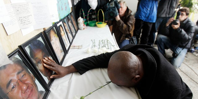 April 10: Efanye Chibuko touches a picture of his wife Doris during a memorial at Oikos University in Oakland, California. Doris Chibuko was among the victims of a shooting rampage at the Oakland school.