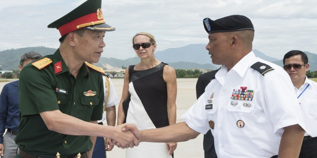U.S. Army Lt. Col. Romel Pajimula, Defense POW/MIA Accounting Agency (DPAA) detachment commander, right, greets Senior Col. Nguyen Huu Luong, Vietnamese Office for Seeking Missing Persons (VNOSMP) Ministry of Defense deputy director, prior to witnessing a repatriation ceremony, Da Nang, Socialist Republic of Vietnam, July 8, 2018.