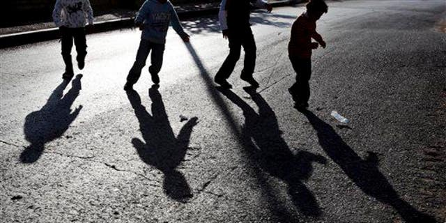 The shadow of Palestinian boys playing with an empty plastic bottle is cast on the street, in the West Bank city of Ramallah, Friday, Nov. 20, 2009. Twenty years after the U.N. adopted a treaty guaranteeing children's rights, fewer youngsters are dying and more are going to school, but an estimated 1 billion children still lack services essential to their survival and development, UNICEF said Thursday. (AP Photo/Muhammed Muheisen)