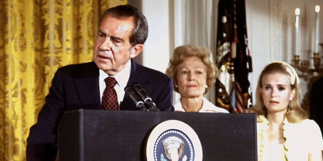 In this file photo, U.S. President Richard Nixon, listened to by First lady Pat Nixon and daughter Tricia Nixon (R), says goodbye to family and staff in the White House East Room on August 9, 1974.