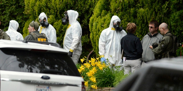 May 18, 2013: During the execution of a search warrant, members of the Joint Federal Haz-Mat Team, FBI, and local law enforcement gather in front of the Osmun Apartments near the intersection of First Avenue and Oak Street in Browne's Addition on Saturday in Spokane, Wash. The search warrant is in connection with ricin-laced letters intercepted at a Post Office facility in Spokane earlier in the week.