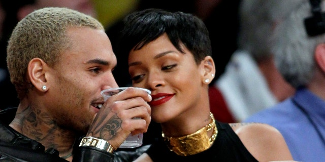 Chris Brown, left, and Rihanna attend an NBA basketball on Dec. 25, 2012.