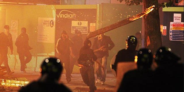 """Sun. 7: A rioter throws a burning wooden plank at police in Tottenham, north London, after members of a community, where a young man was shot dead by police, took to the streets to demand """"justice."""""""