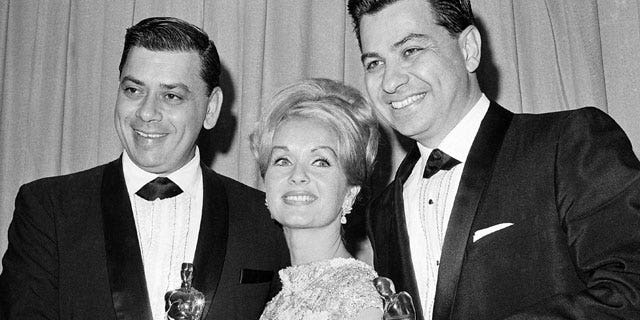 In this April, 5,1965 file photo actress Debbie Reynolds poses with Academy awards winners for best music Richard M. Sherman, right and Robert Sherman, left, who received the award for Mary Poppins in Santa Monica Calif.