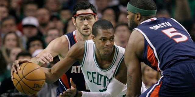 April 11, 2012: Boston Celtics guard Rajon Rondo (9) looks to pass against the double-team by Atlanta Hawks guard Kirk Hinrich and forward Josh Smith (5) during the first half of an NBA basketball game in Boston.