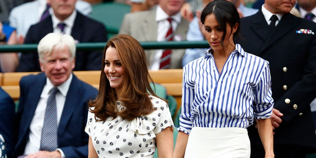 Kate, Duchess of Cambridge, right, and Meghan, Duchess of Sussex take their seats in the Royal Box on Centre Court ahead of the women's singles final.