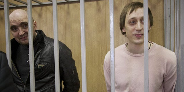 December 3, 2013: Pavel Dmitrichenko, right, a star dancer convicted of ordering a Jan. 17 acid attack on the Bolshoi Ballet's artistic director Sergei Filin, and Andrei Lipatov, stand in a cage at a court room in Moscow, Russia. (AP Photo)
