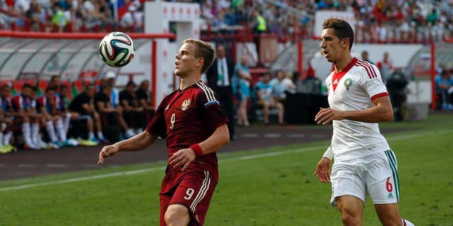Russia's Alexander Kokorin, left,  fights for the ball with Zouhair Feddal,  from Morocco during a friendly soccer match in Moscow, Russia, Friday, June 6, 2014. This is the last friendly match before Russia team leaving for Brazil to compete in the World Cup. (AP Photo/Name)
