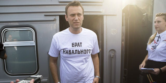 "July 17, 2013: Russian opposition activist Alexei Navalny, wearing a T-shirt reading ""Navalny's Brother"" speaks to supporters and the media at the Yaroslavsky railway terminal in Moscow. (AP Photo/Alexander Zemlianichenko Jr)"