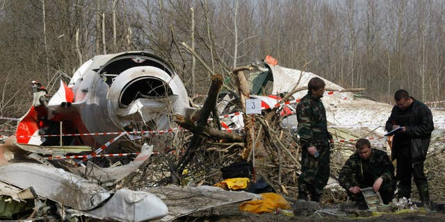 April 11, 2010: Russian investigators work near the wreckage of the Polish presidential plane, that crashed just outside the Smolensk airport in Russia. Russian officials investigating the airplane crash that killed Polish President Lech Kaczynski have now released a report that places the blame on the Poles alone.