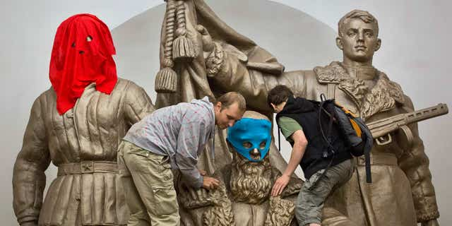 Aug. 17, 2012: Pussy Riot punk group supporters place masks on a monument to WWII heroes to resemble Pussy Riot members, at an underground station in Moscow.