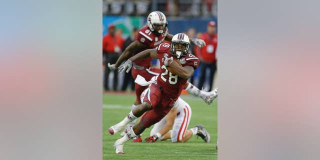 FILE - In this Jan. 1, 2014, file photo, South Carolina running back Mike Davis (28) gains yardage against Wisconsin during the second half of the Capital One Bowl NCAA college football game in Orlando, Fla. Steve Spurrier says 1,000-yard rusher Mike Davis hasn't practiced this week and might not be ready when the ninth-ranked Gamecocks open the season against No. 21 Texas A&M in a week.  (AP Photo/John Raoux, File)