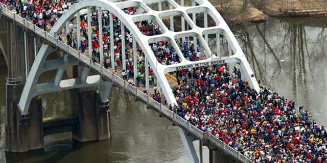 """In this aerial view, Crowds of people move in a symbolic walk across the Edmund Pettus Bridge, Sunday, March 8, 2015, in Selma, Ala. This weekend marks the 50th anniversary of """"Bloody Sunday,' a civil rights march in which protestors were beaten, trampled and tear-gassed by police at the Edmund Pettus Bridge, in Selma.  (AP Photo/Butch Dill)"""