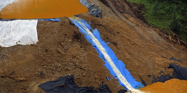 Water flows through a series of retention ponds built to contain and filter out heavy metals and chemicals from the Gold King mine wastewater accident, in the spillway about 1/4 mile downstream from the mine, outside Silverton, Colo., Wednesday, Aug. 12, 2015. The Environmental Protection Agency has taken full responsibility for the mine waste spoiling rivers downstream from Silverton, but people who live near the idled and leaking Gold King mine say local authorities and mining companies spent decades spurning federal cleanup help. (AP Photo/Brennan Linsley)