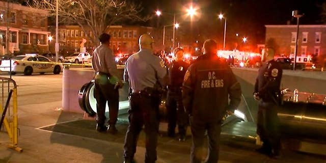 """In this still image taken from video, police and fire officials stand outside the entrance to the Potomac Avenue Metro Station, Thursday night, March 12, 2015 in Washington.  Transit police in Washington, D.C. fatally shot a man after responding to a call about an """"unauthorized person"""" on the tracks in a subway tunnel.  (AP Photo/WJLA-TV)"""