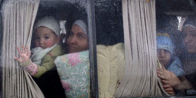 Dec. 20, 2012: Syrian refugees, who fled their home in Idlib due to a government airstrike, look out of a vehicle window just after crossing the border from Syria to Turkey.
