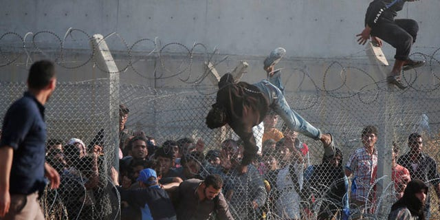 June 14: Syrian refugees cross into Turkey from Syria over and through a hole on the border fence in southeastern Turkey.