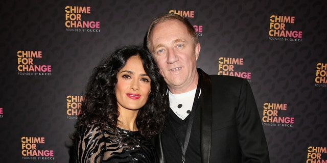"""Salma Hayek Pinault and Francois Henri Pinault arrive at the Royal Box photo wall ahead of the """"Chime For Change: The Sound Of Change Live"""" Concert at Twickenham Stadium on June 1, 2013 in London, England."""