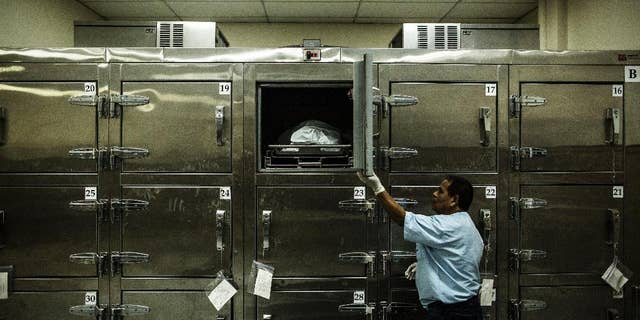FILE - In this May 26, 2015 file photo, a forensic worker closes a morgue refrigerator door after placing a suspected gang member's body inside at the Institute of Legal Medicine in San Salvador, El Salvador. Authorities said on Wednesday, Aug. 19, 2015 that at least 125 people have been killed in the last three days as a wave of violence continues to plague the Central American nation. (AP Photo/Manu Brabo, File)