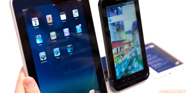 A journalist compares the new Samsung Galaxy Tab, right, a tablet computer to compete with the Apple iPad, left, at IFA, the world's largest trade fair for consumer electronics and electrical home appliances, in Berlin, Germany, Thursday, Sept. 2, 2010. IFA takes place from Sept. 3 to Sept. 8, 2010 on the Berlin Exhibition Grounds.