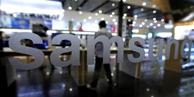 A customer looks at Samsung Electronics' products at a shop at the company's headquarters in Seoul October 7, 2011.
