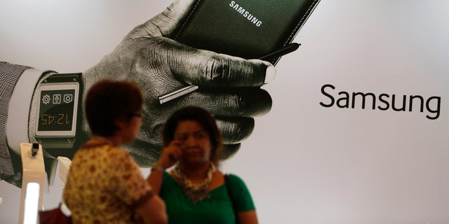 Women stand in front of an ad during the launch of the Samsung Galaxy Note 3 and Galaxy Gear in Jakarta, September 26, 2013.
