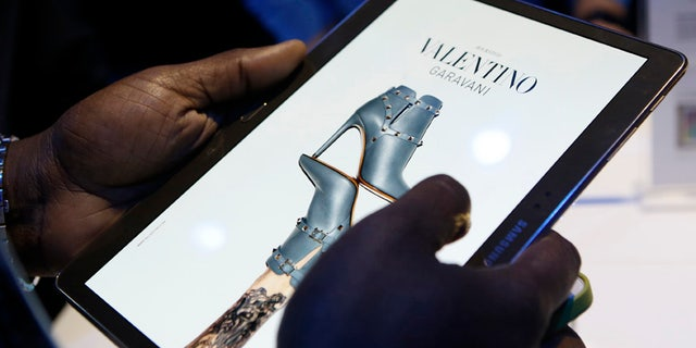 A member of the media scrolls through a fashion magazine during the debut of the Samsung Galaxy Tab S after the product's press debut in New York, Thursday, June 12, 2014.