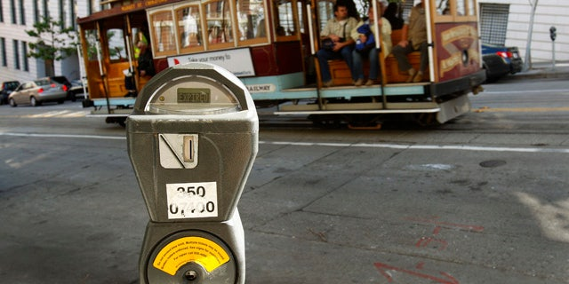 FILE - In this Oct. 27, 2009 file photo, a cable car passes a parking meter near San Francisco's financial district. (AP Photo/Ben Margot, File)