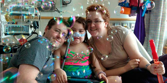 In this file photo provided by the Murnaghan family, Sarah Murnaghan, center, celebrates the 100th day of her stay in Children's Hospital of Philadelphia with her father, Fran, left, and mother, Janet.