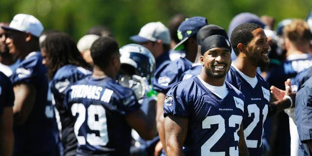 Seattle Seahawks strong safety Jeron Johnson (23) stands with teammates as the huddle breaks up following a session of NFL football training camp, Tuesday, Aug. 5, 2014, in Renton, Wash. (AP Photo/Ted S. Warren)