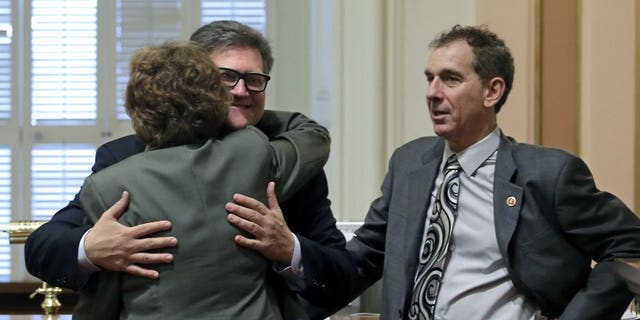 Hertzberg hugs state Sen. Lois Wolk, D-Davis, as Sen. Bob Wieckowski, D-Fremont, looks on at the Capitol in Sacramento, Calif., April 30, 2015.