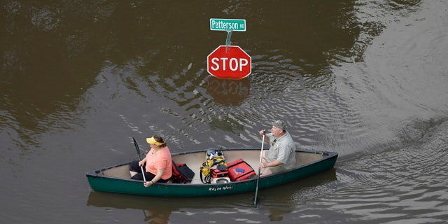 May 30, 2015: In this aerial photo, people canoe through floodwaters past a stop sign near Bear Creek Park in Houston. (AP Photo/David J. Phillip)