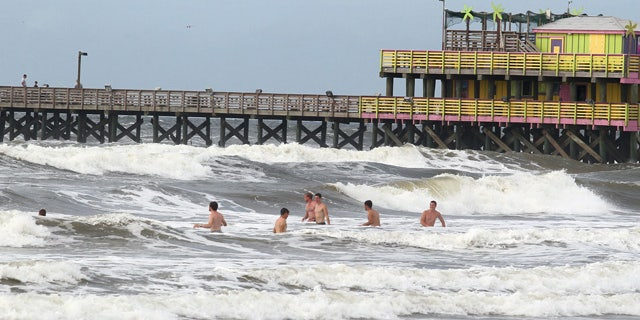 Rough surf doesn't deter swimmers near the 61st Street Pier in Galveston, Texas, on Monday, June 15, 2015, as a tropical disturbance approaches the gulf coast. Beach patrol lifeguards cautioned visitors to only venture in to their waists. A low pressure area located over the south central Gulf of Mexico is being monitored by the National Hurricane Center for possible tropical cyclone formation as it moves northwest towards the middle and upper Texas coast. (Jennifer Reynolds/The Galveston County Daily News via AP)