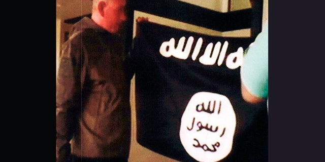 Army Sgt. 1st Class Ikaika Kang holds an Islamic State group flag after allegedly pledging allegiance to the terror group at a house in Honolulu on July 8, 2017. Kang plead guilty Wednesday, as charged in an indictment last year. He is agreeing to a 25-year sentence for charges that could have put him in prison for life.