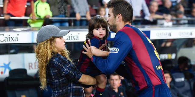 BARCELONA, SPAIN - OCTOBER 18:  Gerard Pique of FC Barcelona passes his son Milan to his wife Shakira during the La Liga match between FC Barcelona and SD Eibar at Camp Nou on October 18, 2014 in Barcelona, Spain.  (Photo by David Ramos/Getty Images)