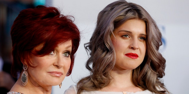 Television host Sharon Osbourne, left, and her daughter Kelly Osbourne pose as they arrive at the 2012 People's Choice Awards in Los Angeles January 11, 2012.