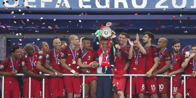 Portugal coach Fernando Santos lifts the trophy between Cristiano Ronaldo, Sunday, July 10, 2016.