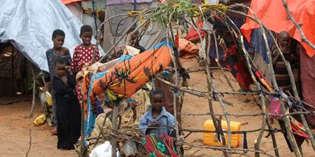 Child from southern Somalia stand near their makeshift shelter at a camp in Mogadishu, Somalia, Monday, Aug 1, 2011. Tens of thousands of famine-stricken Somali refugees were cold and drenched after torrential rains overnight pounded their makeshift structures in the capital, Mogadishu. Rains are needed to plant crops and alleviate the drought that is causing famine in Somalia but on Saturday night the rains added to the misery of refugees who live in structures made of sticks and pieces of cloth.